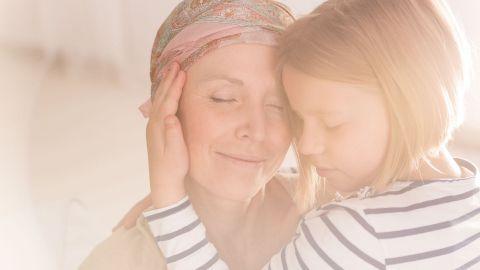 Akute lymphatische Leukämie bei Erwachsenen: Eine Frau mittleren Alters und ein Mädchen umarmen sich. Beide haben die Augen geschlossen. Die Frau trägt ein Kopftuch und lächelt. Das Mädchen berührt mit einer Hand die Wange der Frau.