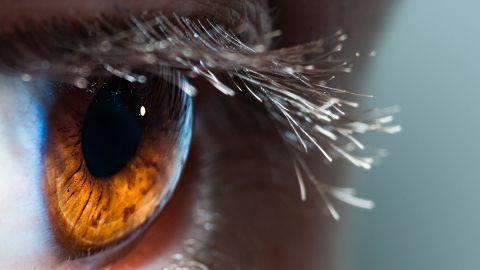 Das Auge eines Menschen in Nahaufnahme. Rund um die schwarze Pupille spiegelt sich ein feuerfarbenes Licht. Am oberen Augenlid erstrecken sich lange Wimpern.