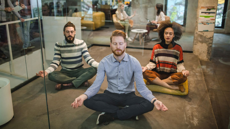 Betriebliche Gesundheitsförderung: 3 Personen sitzen in einem verglasten Raum in einem Bürogebäude auf dem Boden. Sie sitzen im Schneidersitz und haben ihre Arme auf den Knien abgestützt. Sie scheinen während der Arbeitszeit zu meditieren.