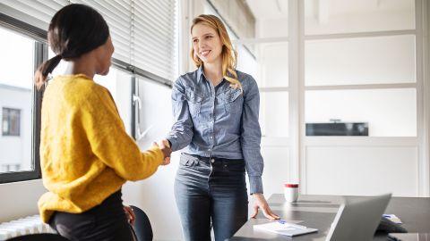 Betriebliches Eingliederungsmanagement: Zwei Frauen stehen an einem Bürotisch und schütteln sich nach einem erfolgreichen geschäftlichen Gespräch zustimmend die Hände.