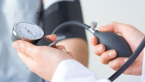 Bluthochdruck: Zwei Hände halten ein Blutdruckmessgerät. Im Hintergrund ist ein Arm zu sehen, an dem die Messmanschette befestigt ist.