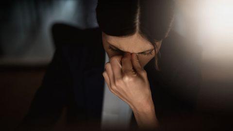 Burn-out: Eine Frau mit gesenktem Kopf fasst sich zwischen Nase und Stirn.