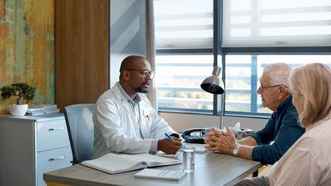 Chronische lymphatische Leukämie (CLL): Ein Arzt sitzt an seinem Schreibtisch und führt ein Gespräch mit einem älterern Mann und einer Frau.