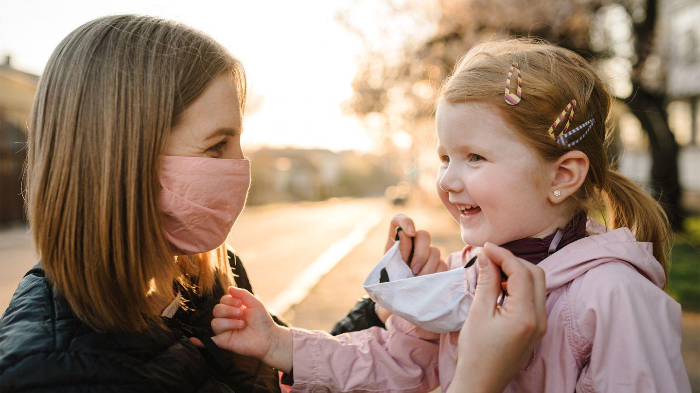 COVID-19: Eine Mutter kniet draußen auf dem Gehweg vor ihrer kleinen Tochter. Die Mutter trägt eine Mund-Nasen-Bedeckung und setzt ihrer Tochter eine Alltagsmaske auf. Beide wirken entspannt und fröhlich.