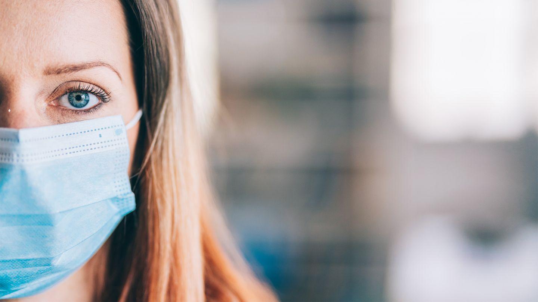 Covid-19 und psychische Gesundheit: Eine junge Frau schaut in die Kamera. Sie trägt einen medizinischen Mund-Nase-Schutz.