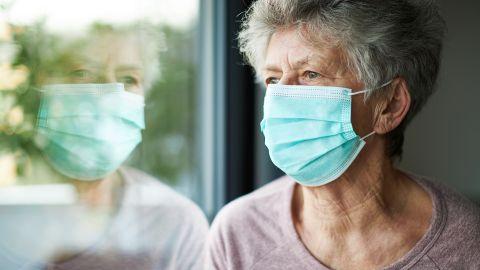 COVID-19: Eine ältere Frau schaut aus dem Fenster. Über Mund und Nase trägt sie einen Mundschutz.