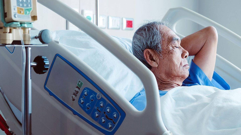 Dekubitus: Ein älterer Mann liegt mit geschlossenen Augen in einem Krankenhausbett.