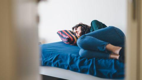 Eine depressiv wirkende Frau liegt auf einem Bett und blickt ins Leere.