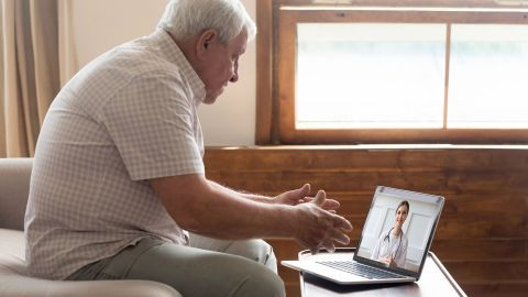 Online-Videosprechstunde: Ein älterer Mann sitzt vor einem Laptop, der auf einem Tisch steht. Auf dem Bildschirm sieht er eine jüngere Frau in einem weißen Kittel, die den Mann anschaut.