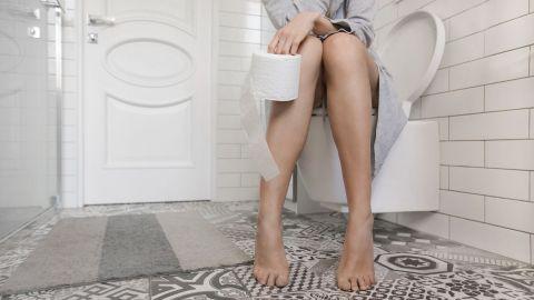Darmkrankheit Divertikulitis: Eine Frau sitzt auf der Toilette und hält eine Rolle Klopapier in der Hand.