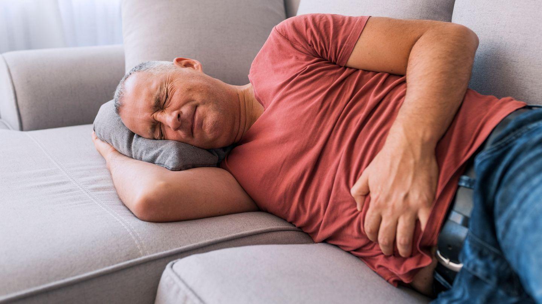 Darmkrankheit Divertikulitis: Ein Mann hält sich mit beiden Händen den Bauch.