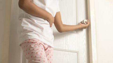 Durchfall: Eine Frau hält sich den Bauch und steht vor einer Toilettentür.