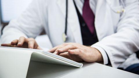 Ein Arzt sitzt am Schreibtisch und tippt etwas auf der Tastatur eines Talbets.