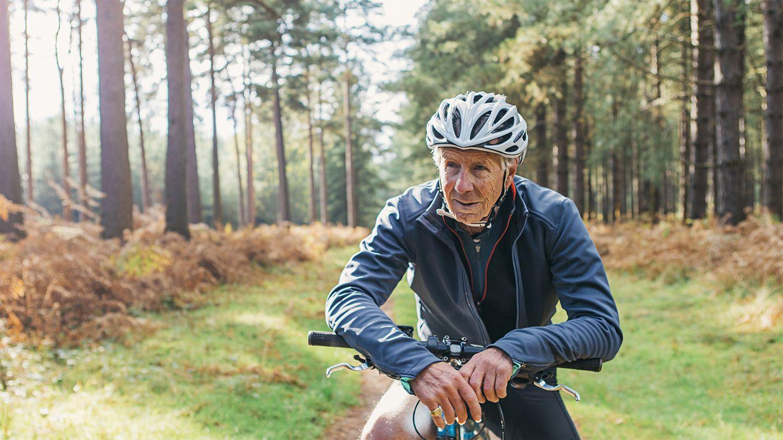 Ernährung und Bewegung im Alter: Ein älterer Mann in Fahrradkleidung pausiert während einer Radtour im Wald und stützt sich dabei auf den Lenker seines Fahrrads.