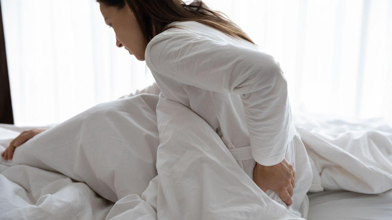 Fibromyalgie: Eine Frau sitzt leicht nach vorne gebeugt in einem Bett. Mit einer Hand fasst sie sich an den Rücken.