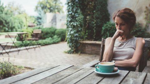 Eine Frau sitzt an einem Tisch in einem Garten, stütz ihren Kopf auf ihrer Hand ab und blickt auf den Tisch. Die Frau scheint besorgt zu sein.