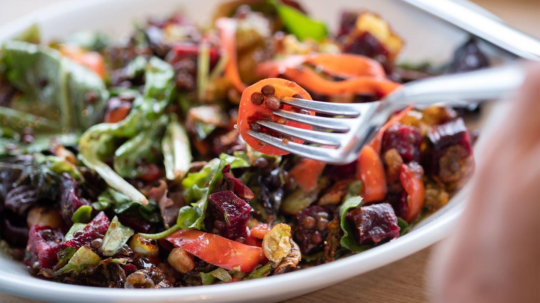 Gesund durch Ernährung: Eine Person piekt mit einer Gabel in einen bunten Salat mit Linsen.