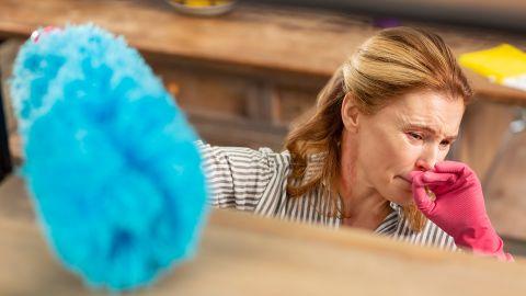 Hausstauballergie: Eine Frau wischt Staub und hält sich die Hand ins Gesicht. Ihre Augen sind gerötet.