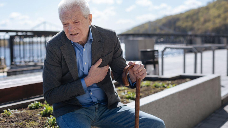Herzschwäche: Ein älterer Mann sitzt auf einem Stein und hält sich mit einer Hand sein Herz. Sein Gesicht ist angespannt und schmerzverzerrt.