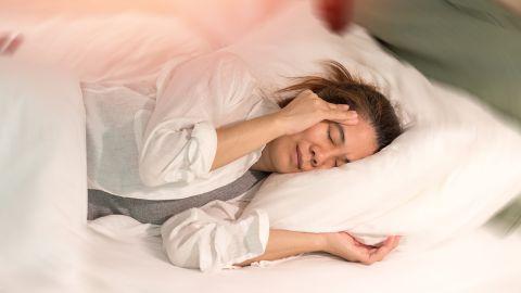 Eine Frau liegt im Bett und fasst sich mit der rechten Hand an ihre Schläfe. Ihre Augen sind geschlossen und ihr Gesicht ist angespannt.