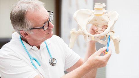 Ein Arzt hält ein künstliches Hüftgelenk in der Hand und zeigt mit einem Stift auf einen bestimmten Knochen.