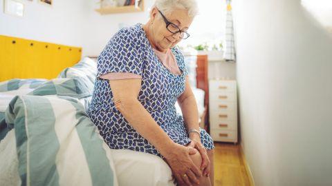 Eine ältere Dame sitzt auf dem Bett und fasst sich an das schmerzende Knie.