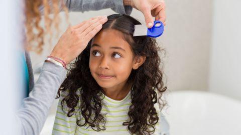 Kopfläuse oder Nissen im Haar: Eine Frau hält einen Kamm in ihrer Hand und kämmt damit das lockige Haar eines Mädchens.