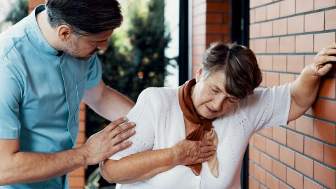 Koronare Herzerkrankung: Eine ältere Frau stützt sich an eine Hausmauer, mit der anderen Hand fasst sie sich an den Brustkorb. Die Frau scheint erschöpft zu sein. Ein jüngerer Mann steht neben ihr und stützt sie an der Schulter.