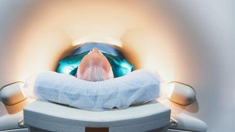 Ein Mann liegt auf dem Rücken in einer engen, mit Licht bestrahlten Röhre für eine MRT-Untersuchung.