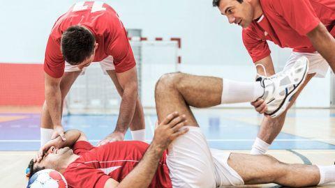 Kreuzbandriss: Ein Fußballer liegt mit schmerzverzerrtem Gesicht auf dem Boden, fasst sich mit einer Hand an den Kopf und mit der anderen Hand an sein Bein. Ein Mitspieler steht daneben und stützt den Fuß des Verletzten.