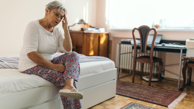 Lagerungsschwindel: Eine ältere Frau sitzt auf einem Bett, beugt ihren Oberkörper leicht nach vorne und fasst sich mit der linken Hand an die Stirn. Die Frau hat ihren Mund leicht geöffnet. Sie wirkt erschöpft.