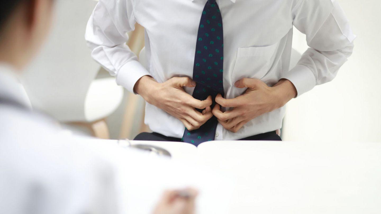 Magenkrebs: Ein Mann greift sich mit beiden Händen an den Bauch. Er scheint starke Schmerzen zu haben.