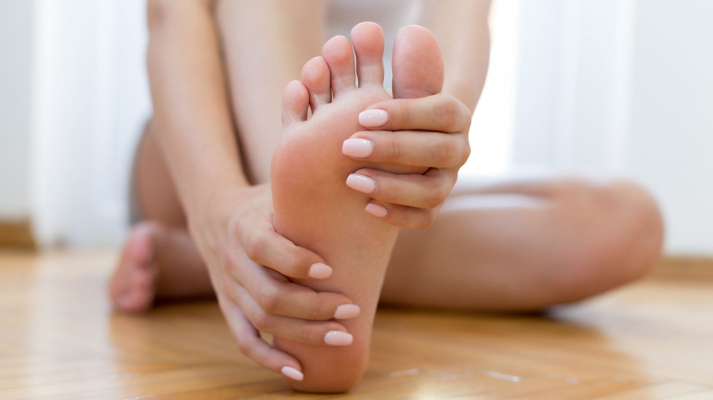 Nagelpilz: Eine Frau sitzt auf dem Boden, streckt ihr Bein nach vorne und schaut auf ihren Fuß.