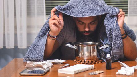 Nasennebenhöhlenentzündung: Ein Mann sitzt an einem Tisch, auf dem Papiertaschentücher, ein Fieberthermometer, Tabletten, eine Flasche Nasentropfen und ein Topf stehen. Der Mann hält ein Handtuch über seinen Kopf, beugt sich über den Topf und inhaliert.