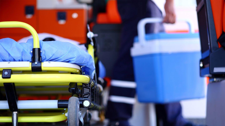 Organspende: Im Vorgergrund ist eine mobile Krankentrage zu sehen. Unscharf und im Hintergrund trägt eine Person einen Kühlbehälter für Transplantationsorgane.
