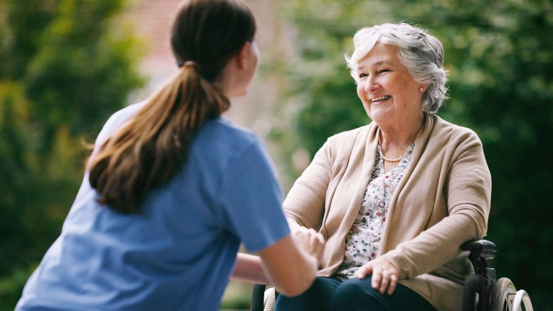 Pflegeversicherung: Eine ältere Frau, die im Rollstuhl sitzt, lächelt eine junge Frau an, die ihr gegenübersitzt. Die junge Frau trägt einen blauen Kittel, ist offenbar eine Pflegerin. Mit beiden Händen drückt sie die rechte Hand der älteren Frau.