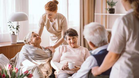 Vollstationäre Pflege im Heim: Zwei ältere Frauen und ein älterer Mann sitzen beisammen in einem Seniorenheim und unterhalten sich. Zwei Pflegerinnen stehen bei den Senioren.
