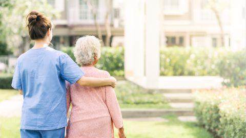 Eine Pflegerin geht mit einer alten Dame in einer Grünanlage spazieren und legt den rechten Arm um ihre Schulter.