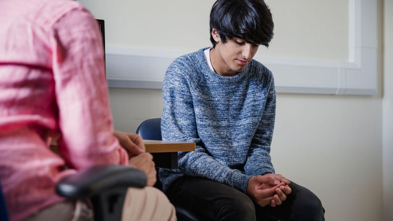 Phimose: Ein Jugendlicher sitzt auf einem Stuhl in einem Behandlungszimmer. Seine Hände liegen in seinem Schoß, er wirkt bedrückt.