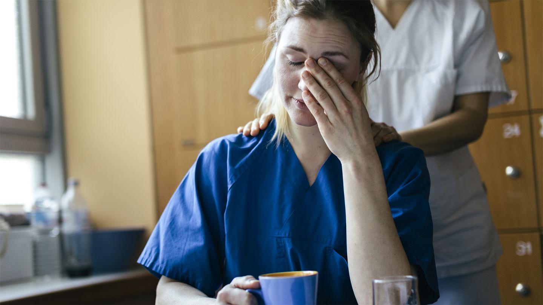 Psychische Gesundheit am Arbeitsplatz: Eine Krankenschwester sitzt mit einer Tasse an einem Tisch. Mit dem linken Ellenbogen stützt sie sich auf und reibt mit ihrer Hand über ihr Gesicht. Eine Kollegin legt ihr von hinten tröstend die  Hände auf die Schul