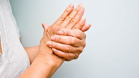 Rheuma: Eine stehende Frau hält beide Arme vor die Brust. Mit einer Hand greift die Frau an das Gelenk der anderen Hand.