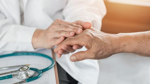 Rheumatoide Arthritis: Ein Arzt sitzt an einem Schreibtisch und untersucht die Hand einer gegenübersitzenden Person. Auf dem Tisch liegt ein Stethoskop.