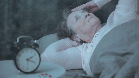 Schlafstörungen: Eine ältere Frau liegt im Bett, fasst sich an den Kopf und schaut an die Decke – neben ihr auf dem Nachttisch steht ein Wecker.