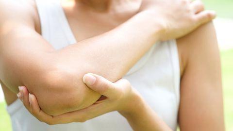 Schleimbeutelentzündung: Eine junge Frau mit sportlicher Kleidung streckt einen Arm nach oben und winkelt den Ellenbogen des Arms an. Mit der anderen Hand stützt sie den Ellenbogen.