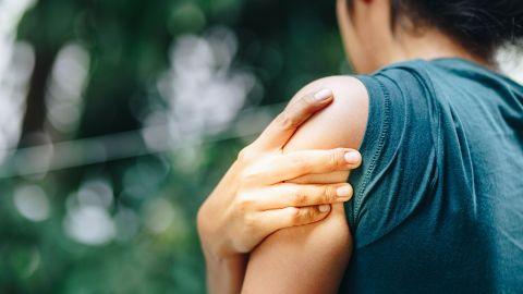 Schulterschmerzen: Eine Frau fasst sich mit ihrer rechten Hand an die schmerzende Schulter.