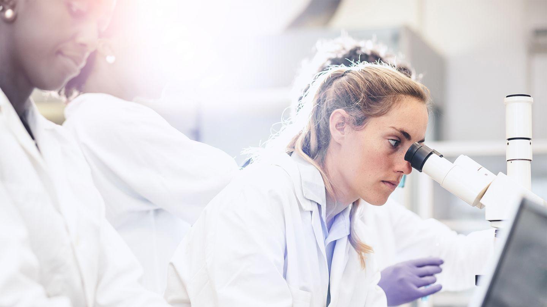 Schwarzer Hautkrebs: Eine Frau sitzt in einem Labor. Sie trägt einen weißen Laborkittel und schaut durch ein Mikroskop. Im Hintergrund sind weitere Labormitarbeiterinnen zu sehen.