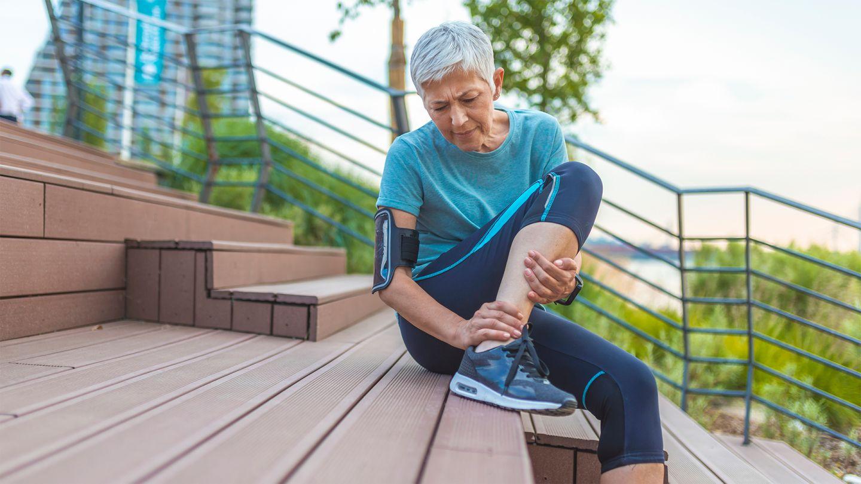 Sehnenreizung: Eine ältere Frau in Sportkleidung sitzt im Freien auf einer Treppe. Sie hält sich den Knöchel, ihr Gesicht ist schmerzverzerrt.