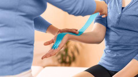 Eine Physiotherapeutin klebt ein blaues Band (Kinesio-Tape) auf das Handgelenk und den Unterarm einer Frau, die auf einer Behandlungsliege in einer Praxis sitzt. Die Patientin hat offenbar einen sogenannten Schnappfinger.