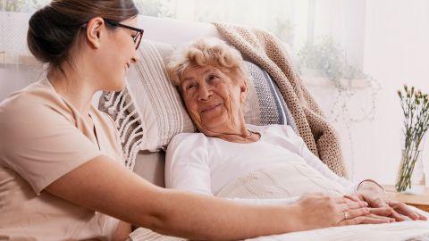 Seltene Krebsarten: Eine ältere Frau liegt in einem Bett. Neben ihr sitzt eine Krankenschwester und hält ihre Hand. Die beiden lächen sich an.