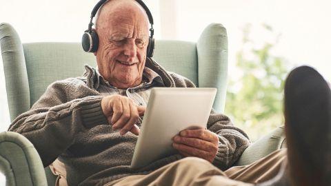 Ein älterer Mann sitzt mit ausgestreckten Beinen auf einem Sessel. Er trägt Kopfhörer und schaut lächelnd auf den Bildschirm eines Laptops, den er in seiner linken Hand hält. Mit dem Zeigefinger der anderen Hand berührt der Mann den Bildschirm.